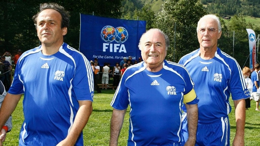 FILE - In this Sunday, Aug. 26, 2007 file photo FIFA President Sepp Blatter, center, UEFA President and French football legend Michel Platini, left, and German soccer legend Franz Beckenbauer, right, arrive for a gala match between FIFA and Team 2000 in the 10th edition of the 'Sepp Blatter Tournament', in Ulrichen, Switzerland.  Sepp Blatter says he will resign from his position amid corruption scandal and is promising to call for fresh elections to choose a successor.  (Laurent Gillieron, Keystone via AP, File)