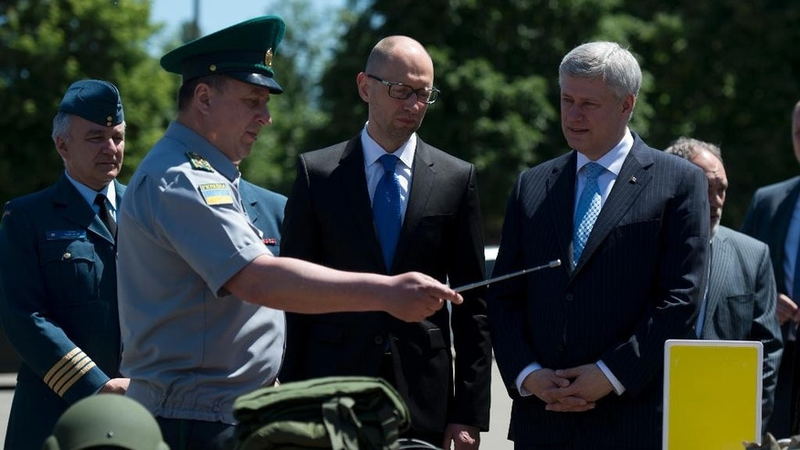 Canadian Prime Minister Stephen Harper and Ukraine Prime Minister Arseniy Yatsenyuk are shown non-lethal military equipment provided by Canada during a visit to the Academic Institute of the National Academy of Internal Affairs of Ukraine for Training of Specialists for Public Safety, Psychological Service and National Guard of Ukraine Units in Kyiv, Ukraine Saturday June 6, 2015.  (Adrian Wyld/The Canadian Press via AP) MANDATORY CREDIT