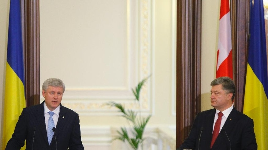 Canadian Prime Minister Stephen Harper, left, makes a statement to the media, with Ukrainian President Petro Poroshenko in Kiev, Ukraine, Saturday, June 6, 2015.  A fresh outbreak of violence between government troops and pro-Russian separatists in eastern Ukraine is threatening to derail an already tenuous cease-fire. (AP Photo/Sergei Chuzavkov)
