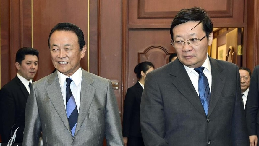 Japanese Deputy Prime Minister and Finance Minister Taro Aso, left, and China's Finance Minister Lou Jiwei prepare for a meeting at Diaoyutai State Guesthouse in Beijing Saturday, June 6, 2015. Chinese and Japanese finance ministers held talks Saturday to deepen economic cooperation that had been delayed for about two years over strained relations between the Asian giants. (Takuro Yabe/Kyodo News via AP) JAPAN OUT, MANDATORY CREDIT