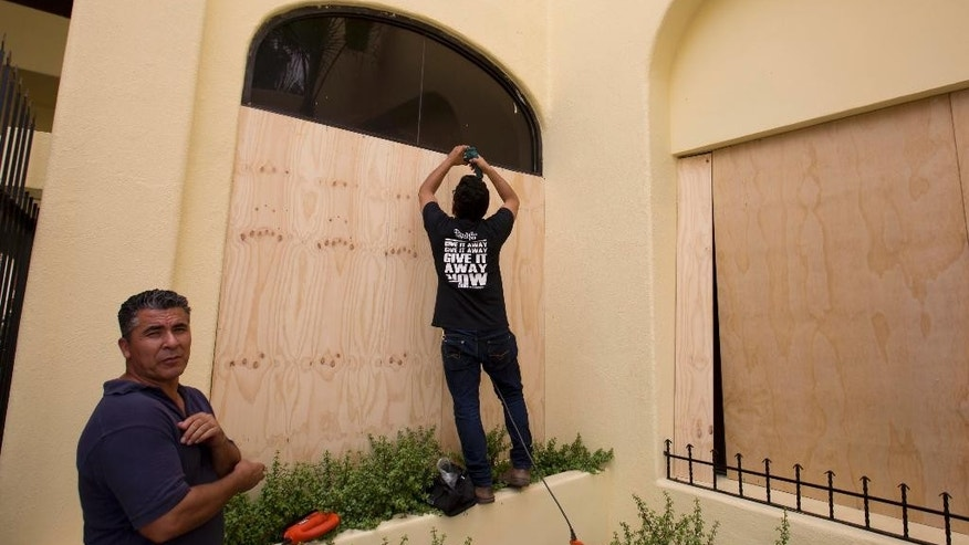 Workers board over store front windows in preparation for Hurricane Blanca, in Cabo San Lucas, Mexico, Saturday June 6, 2015. The unpredictable Blanca, which strengthened suddenly from a Category 1 to a Category 4 storm on Saturday before weakening slightly, is expected to make landfall as a tropical storm on Monday. But authorities said its outer bands could start hitting the southern Baja California Peninsula as a hurricane on Sunday. (AP Photo/Eduardo Verdugo)