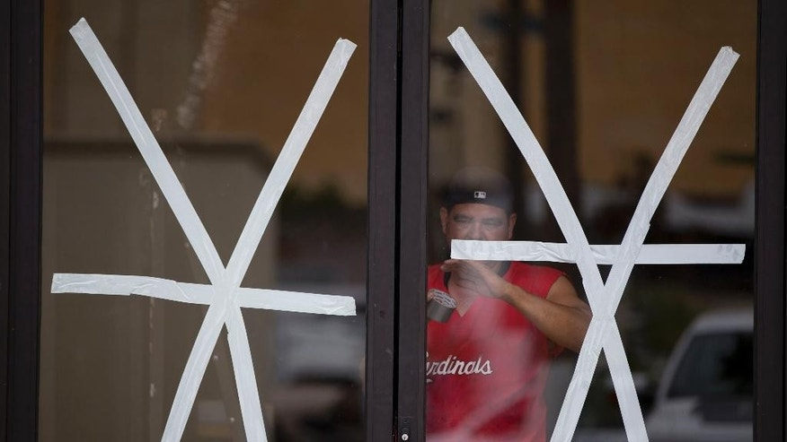 A man lays down tape to reinforce storefront windows against Hurricane Blanca in Cabo San Lucas, Mexico, Saturday June 6, 2015. The unpredictable Blanca, which strengthened suddenly from a Category 1 to a Category 4 storm on Saturday before weakening slightly, is expected to make landfall as a tropical storm on Monday. But authorities said its outer bands could start hitting the southern Baja California Peninsula as a hurricane on Sunday. (AP Photo/Eduardo Verdugo)