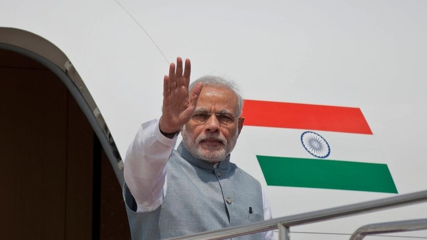 Indian Prime Minister Narendra Modi waves to the gathering upon arrival at the Hazrat Shahjalal International airport in Dhaka, Bangladesh, Saturday, June 6, 2015. Modi is on a  two-day official visit to Bangladesh. (AP Photo/A.M. Ahad)