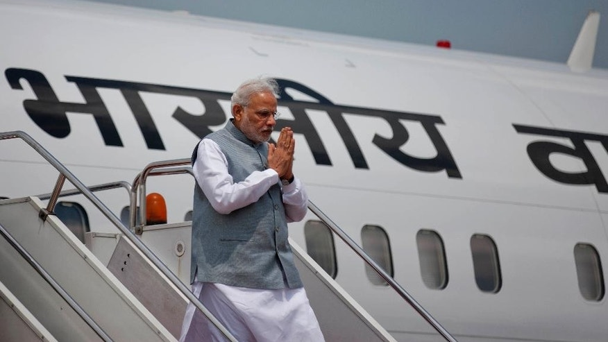 Indian Prime Minister Narendra Modi gestures upon arrival at the Hazrat Shahjalal International airport in Dhaka, Bangladesh, Saturday, June 6, 2015. Modi is on a  two-day official visit to Bangladesh. (AP Photo/A.M. Ahad)