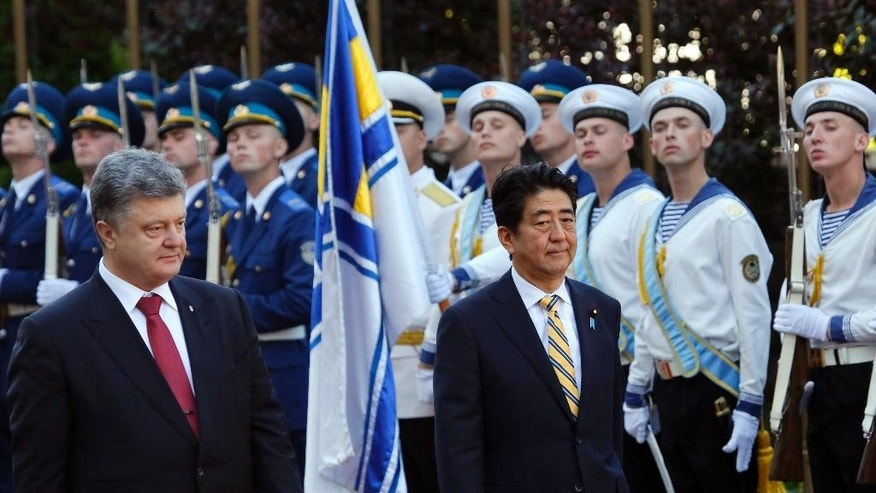 Ukrainian President Petro Poroshenko, left, and Japan's Prime Minister Shinzo Abe review the honor guard during a welcome ceremony ahead of their meeting in Kiev, Ukraine, Saturday, June 6, 2015. (AP Photo/Sergei Chuzavkov)
