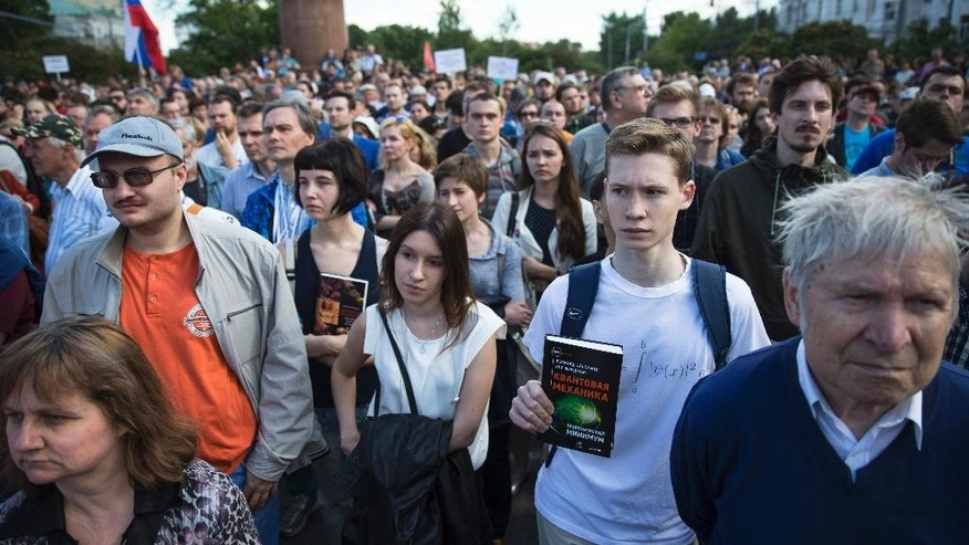 People gather at a rally against existing science and education policies in Moscow, Russia, Saturday, June 6, 2015. Demonstrators, holding a posters and textbooks, rallied in support of the Dynasty Foundation which develops fundamental science and education in Russian, and which has been added to the list of Russian organizations considered foreign agents. (AP Photo/Pavel Golovkin)