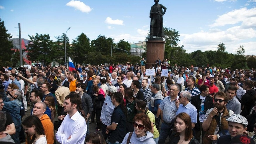 "People gather at a rally against existing science and education policies in Moscow, Russia, Saturday, June 6, 2015. Demonstrators, holding a poster saying  ""Bury the science - bury the country,"" and textbooks, rallies in support of the Dynasty Foundation which develops fundamental science and education in Russian, and which has been added to the list of Russian organizations considered foreign agents. In the background is a monument to famous Russian general Alexander Suvorov. (AP Photo/Pavel Golovkin)"