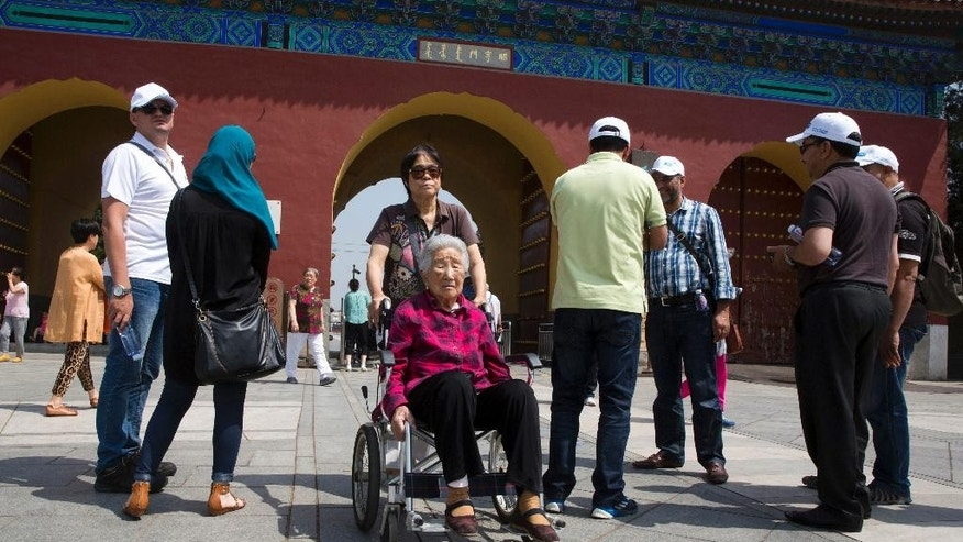 In this photo taken Friday, June 5, 2015, an elderly Chinese woman is pushed in a wheelchair near the entrance to the Temple of Heaven park in Beijing. The number of senior tourists in China jumped by 58 percent last year compared to 2013, according to the state-run China Daily newspaper, and 62 percent of Chinese senior citizens join organized tours. (AP Photo/Ng Han Guan)