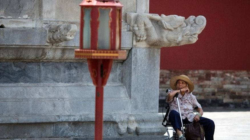 In this photo taken Friday, June 5, 2015, an elderly Chinese woman rests in a wheelchair at the Temple of Heaven park in Beijing. The number of senior tourists in China jumped by 58 percent last year compared to 2013, according to the state-run China Daily newspaper, and 62 percent of Chinese senior citizens join organized tours. (AP Photo/Ng Han Guan)