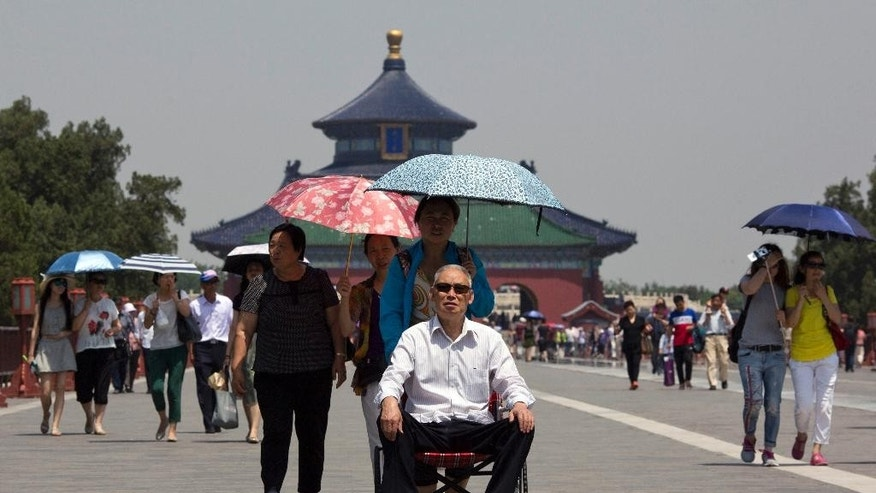 In this photo taken Friday, June 5, 2015, an elderly man is pushed in a wheelchair at the Temple of Heaven park in Beijing. The number of senior tourists in China jumped by 58 percent last year compared to 2013, according to the state-run China Daily newspaper, and 62 percent of Chinese senior citizens join organized tours. (AP Photo/Ng Han Guan)