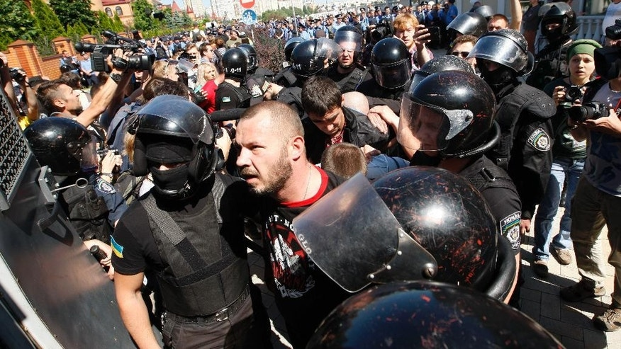 Policemen detain opponents of a gay rights march, in Kiev, Ukraine, Saturday, June 6, 2015. Opponents of a gay rights march held in the Ukrainian capital have thrown smoke bombs and tear gas and the Interfax news agency cites police as saying five officers were injured in the clash. (AP Photo/Vladimir Donsov)