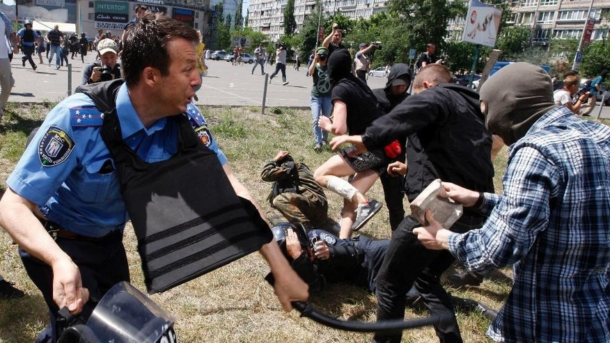A policemen clashes with an opponent of a gay rights march, in Kiev, Ukraine, Saturday, June 6, 2015. Opponents of a gay rights march held in the Ukrainian capital have thrown smoke bombs and tear gas and the Interfax news agency cites police as saying five officers were injured in the clash. (AP Photo/Vladimir Donsov)