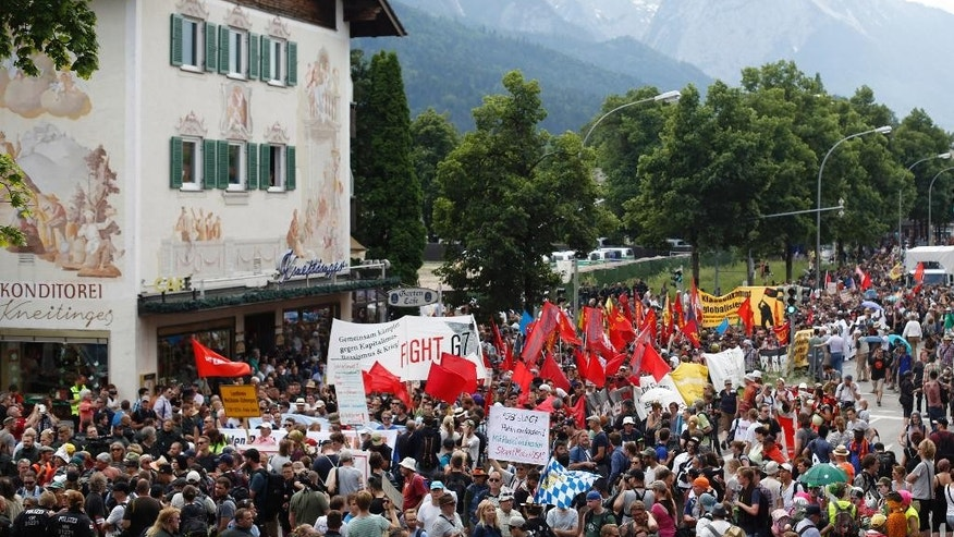 Police officers briefly stop a protest  in Garmisch-Partenkirchen, southern Germany, Saturday, June 6, 2015 against the G-7 summit in nearby Schloss Elmau hotel on June 7/8. (AP Photo/Markus Schreiber)
