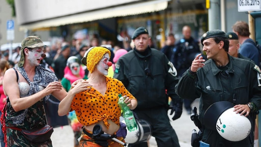 A demonstrator dressed as clown chats with a police officer during a protest  in Garmisch-Partenkirchen, southern Germany, Saturday, June 6, 2015 against the G-7 summit in nearby Schloss Elmau hotel on June 7/8. (AP Photo/Matthias Schrader)