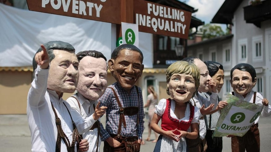 Demonstrators wear masks of Canadian Prime Minister Stephen Harper, British Prime Minister David Cameron, U.S. President Barack Obama, German Chancellor Angela Merkel, French President Francois Hollande, Japanese Prime Minister Shinzo Abe and Italian Prime Minister Matteo Renzi, from left, during a Oxfam demanding the fight against poverty in Garmisch-Partenkirchen, southern Germany, Saturday, June 6, 2015 where the G-7 summit will take place in nearby Schloss Elmau hotel on June 7/8. (AP Photo/Markus Schreiber)