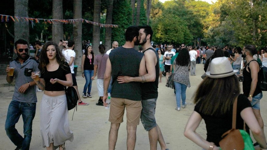Two men kiss they take part in a second gay pride parade in downtown Nicosia, Cyprus, Saturday, June 6, 2015. Several thousand people marched in the streets of Cyprus' capital for the east Mediterranean island nation's 2nd gay pride parade as detractors stayed away. (AP Photo/Petros Karadjias)