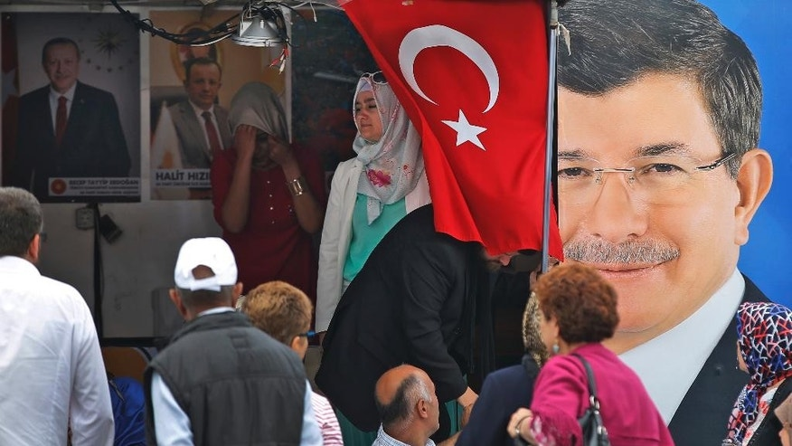 People walk past a poster of Turkey's Prime Minister and leader of the Justice and Development Party (AKP) Ahmet Davutoglu, right, in Istanbul, Turkey, Friday, June 5, 2015. Turkey will hold a general election on Sunday June 7 and approximately 56 million Turkish voters are eligible to cast their ballots to elect the 550 members of the Grand National Assembly. (AP Photo/Emrah Gurel)