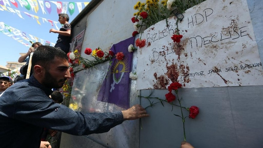 A man places carnations at the explosion site  as supporters of pro-Kurdish Peoples' Democracy Party, HDP,  march to protest the death of two people in two explosions during an HDP election rally a day ago, in Dirabakir, Turkey, Saturday, June 6, 2015. It comes at a tense time, two days before Sunday's parliamentary elections in Turkey, in which the Kurdish votes will be critical. (AP Photo/Emre Tazegul)