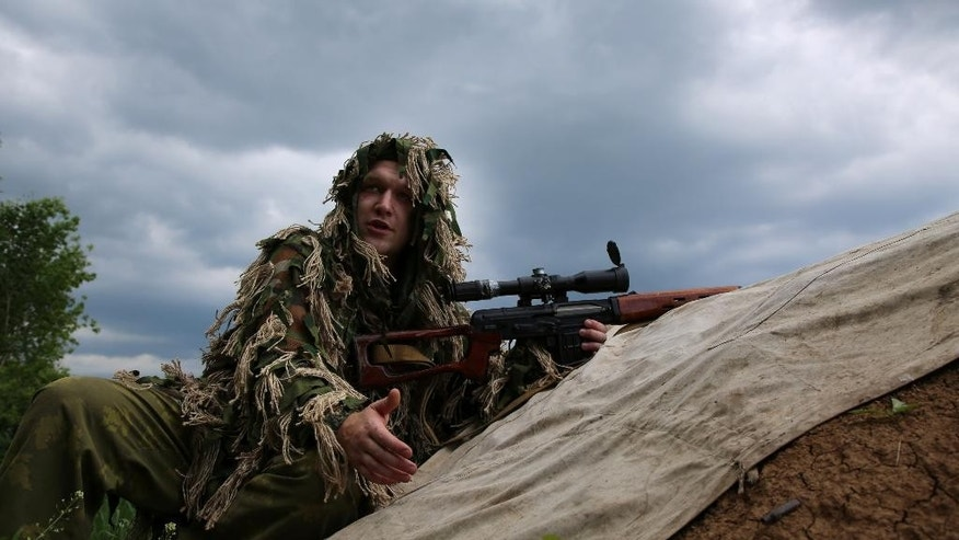 A separatist sniper in eastern Ukraine talks at his position in the town of Dokuchayevsk, Ukraine, on Friday, June 5, 2015. A tense calm is holding in the east of the country in the days after a bloody battle Wednesday between separatist and government forces erupted in a suburb of the main rebel stronghold of Donetsk. (AP Photo/Peter Leonard)