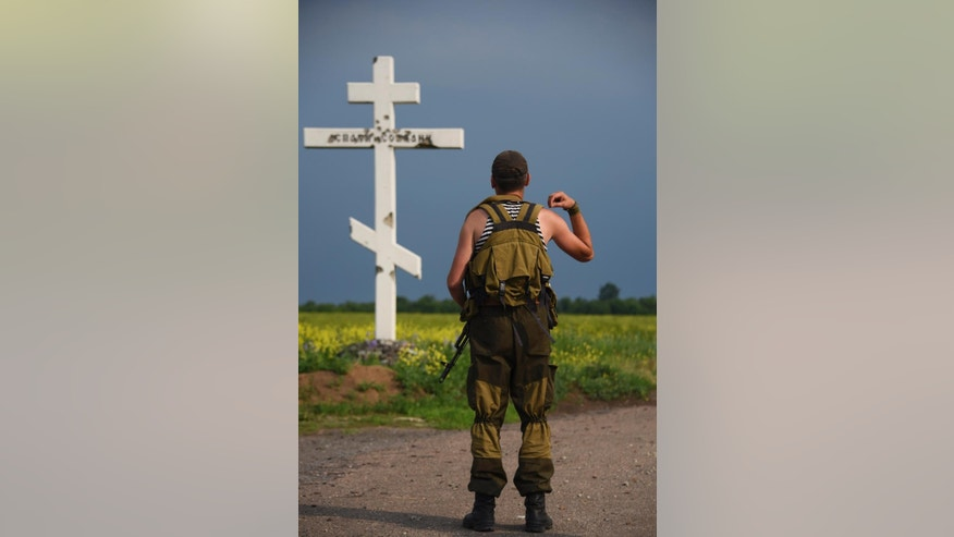 A Russia-backed rebel crosses himself in front of the cross near the division line with the Ukrainian army near Dokuchayevsk, eastern Ukraine, Friday, June 5, 2015. As fears persist that eastern Ukraine is about to fall back into full-scale war, a leader of the international monitoring group is urgently calling for resumed negotiations. (AP Photo/Mstyslav Chernov)