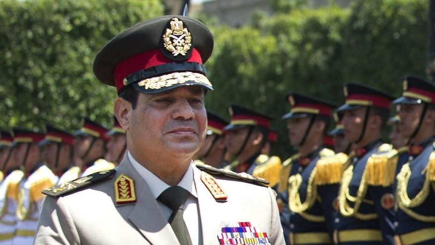 FILE - In this April 24, 2013, file photo, Egyptian Defense Minister Gen. Abdel-Fattah el-Sissi reviews honor guards during an arrival ceremony for his U.S. counterpart at the Ministry of Defense in Cairo. A year after the general-turned-politician took office after a landslide election win, el-Sissi has effectively shut down politics and is running the country as a one-man show, a far cry from the democracy millions dreamed of when they toppled autocrat Hosni Mubarak in a stunning 2011 uprising. (Jim Watson/Pool Photo via AP, File)