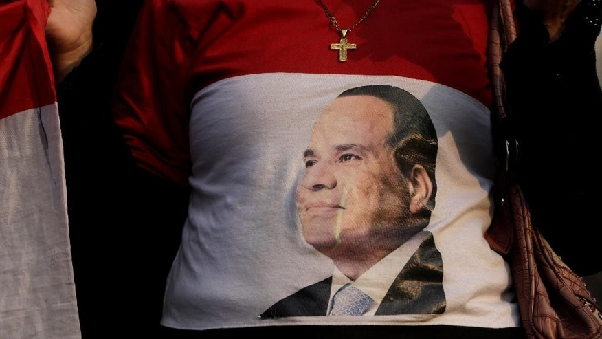 FILE - In this Feb. 17, 2015, file photo, an Egyptian Christian woman wears a shirt with a photo of Egyptian President Abdel Fattah el-Sissi during a vigil to mourn Christians who were killed in Libya, at St. Mark's Cathedral in Cairo. A year after the general-turned-politician took office after a landslide election win, el-Sissi has effectively shut down politics and is running the country as a one-man show, a far cry from the democracy millions dreamed of when they toppled autocrat Hosni Mubarak in a stunning 2011 uprising. (AP Photo/Amr Nabil, File)
