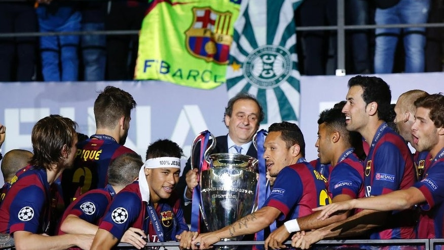UEFA President Michel Platini prepares to hand over the trophy after the Champions League final soccer match between Juventus Turin and FC Barcelona at the Olympic stadium in Berlin Saturday, June 6, 2015. Barcelona won the match 3-1. (AP Photo/Luca Bruno)