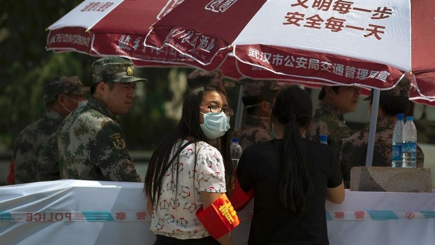 In this Saturday, June 6, 2015 photo, a volunteer wearing a mask looks back as she stands near the soldiers guarding outside the mortuary where bodies of passengers aboard the capsized Eastern Star cruise ship are taken, in Jianli county of southern China's Hubei province. As the closest town to the site of Monday's Yangtze River cruise ship disaster, Jianli is the staging area for what began as a rescue effort, but which has now shifted to identifying the remains of the more than 430 people killed when the ship capsized in a freak tornado. Just 14 people survived in what is now officially China's worst maritime disaster in nearly seven decades. (AP Photo/Andy Wong)