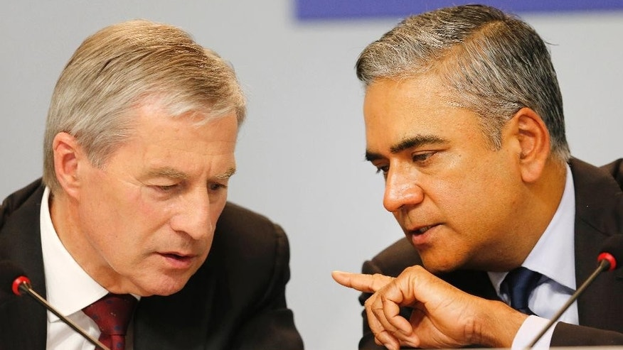 FILE - In this April 27, 2015 file phtoo Co-CEOs of Deutsche Bank Anshu Jain, right, and Juergen Fitschen talk to each other during a press conference about the further strategies of the bank in Frankfurt, Germany. Deutsche Bank said Sunday, June 7, 2015 that Jain and Fitschen will resign.  John Cryan will succeed Jain in July 2015 and will become the sole CEO in May 2016. (AP Photo/Michael Probst)