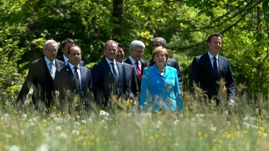 European Commission President Jean-Claude Juncker, left, Italian Prime Minister Matteo Renzi, hidden, French President Francois Hollande, European Council President Donald Tusk, Canadian Prime Minister Stephen Harper, United States President Barack Obama, German Chancellor Angela Merkel and Birtish Prime Minister David Cameron, right,  walk to a group photo at the Schloss Elmau near Garmisch, Germany at the G7 Summit Sunday June 7, 2015.  (Adrian Wyld/The Canadian Press via AP)