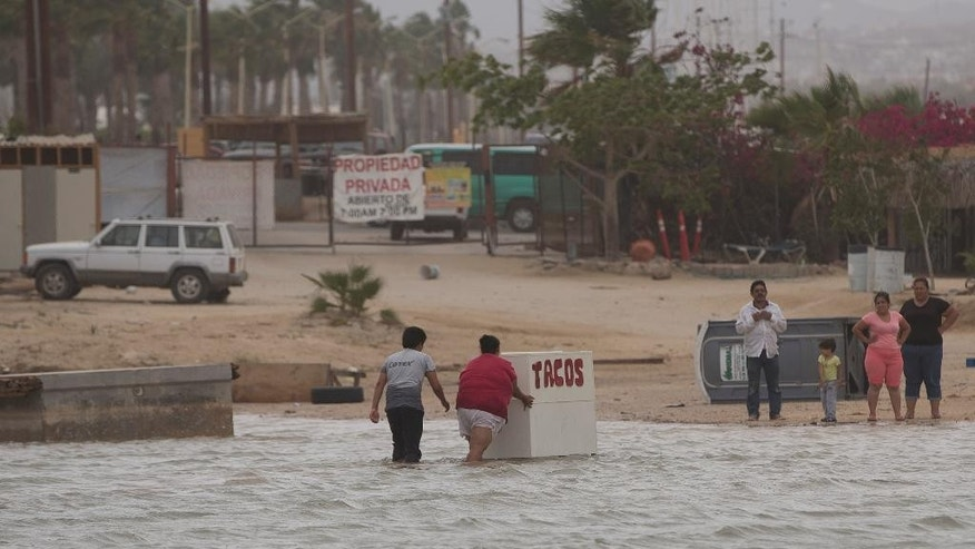 People salvage some of their belongings after rising seas overnight from Hurricane Blanca, in Cabo San Lucas, Mexico, Sunday June 7, 2015. The unpredictable storm strengthened rapidly to a Category 4 storm on Saturday, but the U.S. National Hurricane Center says it has since weakened to Category 1 with top winds near 90 mph. (AP Photo/Eduardo Verdugo)
