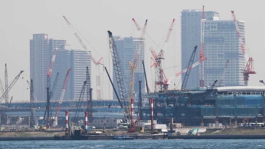 In this Friday, March 27, 2015 photo, cranes stand in a construction site on the reclaimed land in Tokyo Bay area. Japan's economy grew at a faster pace than initially estimated in the January-March quarter, expanding at a 3.9 percent annual rate on stronger consumer and corporate spending. The revision announced Monday, June 8 by the Cabinet Office was sharply higher than the 2.4 percent pace initially reported. (AP Photo/Koji Sasahara)