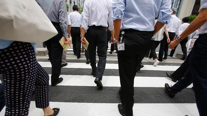 Office workers walk on a pedestrian crossing during a lunch break in Tokyo Monday, June 8, 2015. Japan's economy grew at a faster pace than initially estimated in the January-March quarter on stronger consumer and corporate spending, though economists anticipate slower growth in April-June. The 3.9 percent annualized growth rate announced Monday by the Cabinet Office was sharply higher than the 2.4 percent pace initially reported. (AP Photo/Shizuo Kambayashi)