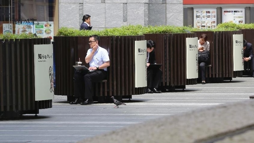 Office workers rest on benches during a lunch break in Tokyo Monday, June 8, 2015. Japan's economy grew at a faster pace than initially estimated in the January-March quarter on stronger consumer and corporate spending, though economists anticipate slower growth in April-June. The 3.9 percent annualized growth rate announced Monday by the Cabinet Office was sharply higher than the 2.4 percent pace initially reported. (AP Photo/Koji Sasahara)