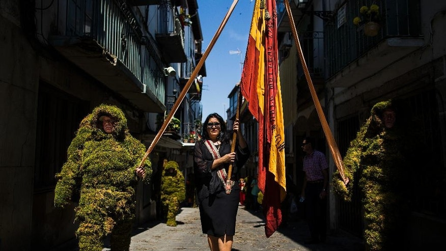 Moss men and a reveler carry Spanish flags as they  take part during the Corpus Christi procession in the small village of Bejar, Spain, Sunday, June 7, 2015. Men covered from head to toe in moss have paraded through the streets of Bejar in western Spain to commemorate a daring raid that local legend says helped liberate their town from Muslim occupation some eight centuries ago. Locals believe that during the reign of King Alfonso VIII of Castile (1155-1214) men camouflaged themselves in moss from local forests to enable them to approach the gates of a Muslim fortress.  (AP Photo/Andres Kudacki)