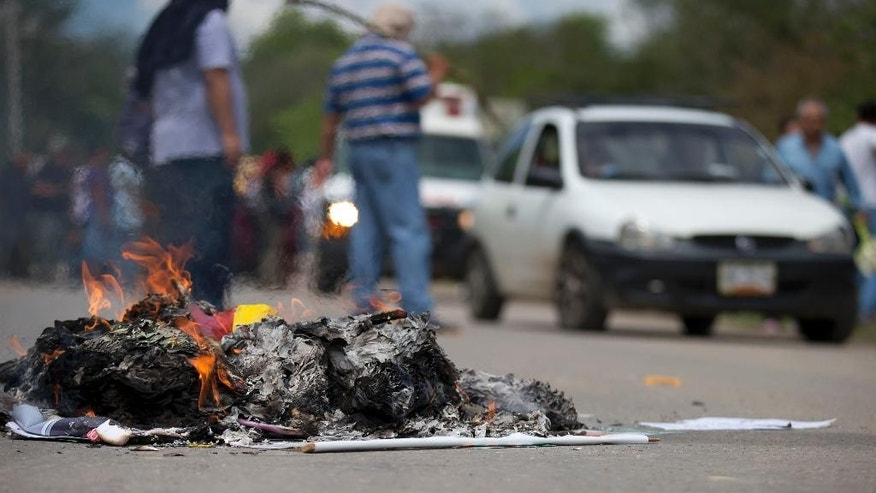 Campaign signs and other election related material confiscated from passing vehicles burn at a roadblock set up by a community group protesting Sunday's elections, in Tixtla, Mexico, Saturday, June 6, 2015. A group of men and women, many with faces covered by bandanas, stopped all traffic entering and leaving the Guerrero state town of Tixtla along one main road, to search for and burn any material related to the elections. (AP Photo/Rebecca Blackwell)