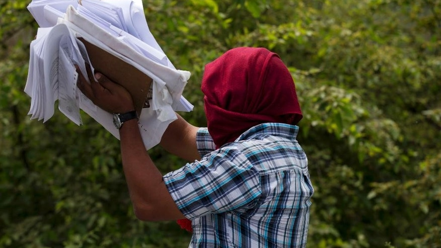 A masked member of a community group protesting Sunday's elections, carries election related papers confiscated from a passing vehicle, at a roadblock at the entrance to Tixtla, Mexico, Saturday, June 6, 2015. Men and women, many with faces covered by bandanas, stopped all traffic entering and leaving the Guerrero state town of Tixtla to search for and burn any election posters or other materials. (AP Photo/Rebecca Blackwell)