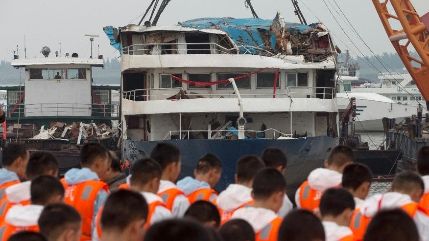 Rescuers bow during a memorial service near the raised capsized ship Eastern Star on the Yangtze River in Jianli county of southern China's Hubei province Sunday, June 7, 2015. China's state broadcaster reports the death toll from a cruise ship disaster has risen above 400, as teams expand the search of the Yangtze River for dozens more missing in China's deadliest maritime disaster in nearly seven decades. (AP Photo/Andy Wong)