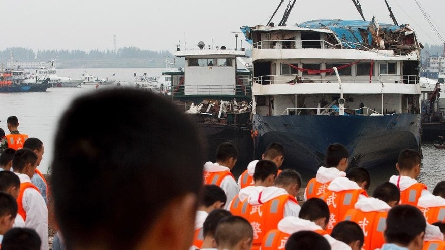 Rescuers bow during a memorial service near the raised capsized ship Eastern Star on the Yangtze River in Jianli county of southern China's Hubei province Sunday, June 7, 2015. China's state broadcaster reports the death toll from the cruise ship disaster has risen above 400, as teams expand the search of the Yangtze River for dozens more missing in China's deadliest maritime disaster in nearly seven decades. (AP Photo/Andy Wong)