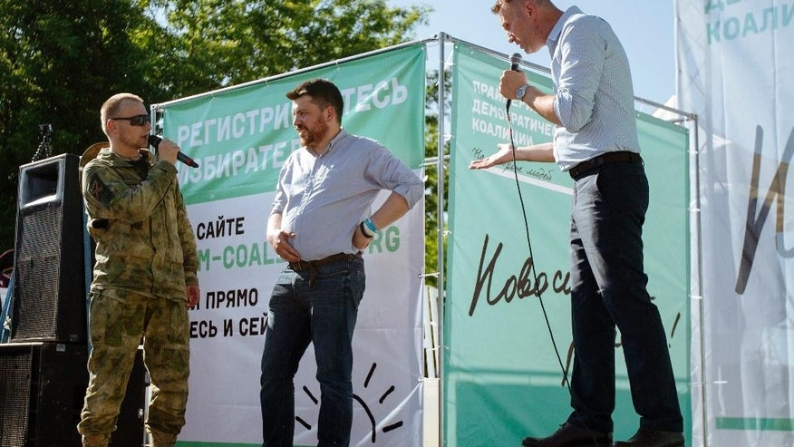 """Russian opposition activist and blogger Alexei Navalny, right, argues with a man in military uniform, left, during a rally in a Novosibirsk park attracted several hundred people in Novosibirsk, Russia, Sunday, June 7, 2015. In his first trip out of Moscow in three years, Russian opposition leader Alexei Navalny has visited Siberia's biggest city to urge voters to participate in primaries that will choose opposition candidates for regional elections. The banner in the background reads """"Novosibirsk decides"""". (AP Photo/Alexander Lukin)"""
