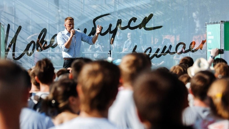 """Russian opposition activist and blogger Alexei Navalny gestures while speaking to a crowd during in a Novosibirsk park attracted several hundred people in Novosibirsk, Russia, Sunday, June 7, 2015. In his first trip out of Moscow in three years, Russian opposition leader Alexei Navalny has visited Siberia's biggest city to urge voters to participate in primaries that will choose opposition candidates for regional elections. The banner in the background reads """"Novosibirsk decides"""". (AP Photo/Alexander Lukin)"""