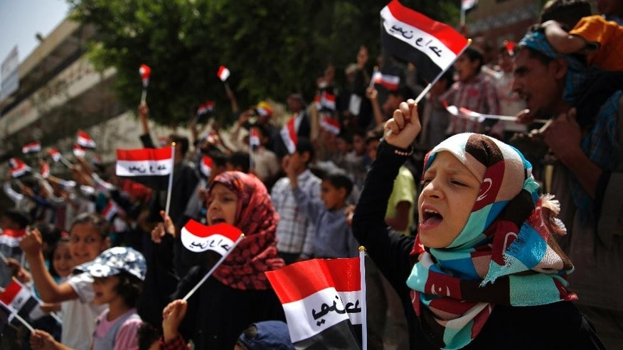 "Yemeni children chant slogans and wave Yemeni flags which have the Arabic, ""Yemen one,"" written on them, during a protest against Saudi-led airstrikes, in Sanaa, Yemen, Saturday, June 6, 2015. (AP Photo/Hani Mohammed)"