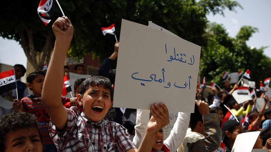 "Yemeni children chant slogans during a protest against Saudi-led airstrikes, in Sanaa, Yemen, Saturday, June 6, 2015. Arabic writing on a banner at left reads ""Don't kill my father and mother."" (AP Photo/Hani Mohammed)"
