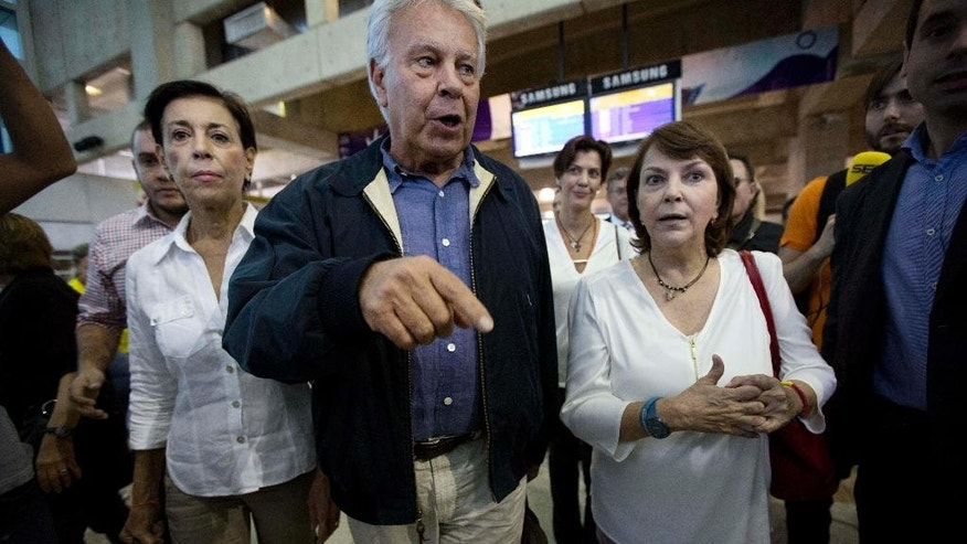 Spain's former president Felipe Gonzalez, center, walks with Antonieta Mendoza de Lopez, the mother of jailed opposition leader Leopoldo Lopez, left, and Mitzy Capriles de Ledezma, wife of imprisoned Caracas Mayor Antoino Ledezma, right,  upon his arrival at Maiquetia International airport in la Guaira, Venezuela, Sunday, June 7, 2015. Gonzalez is visiting Venezuela where he expects to visit the imprisoned mayor Caracas, Antonio Ledezma and jailed opposition leader Leopoldo Lopez. (AP Photo/Ariana Cubillos)
