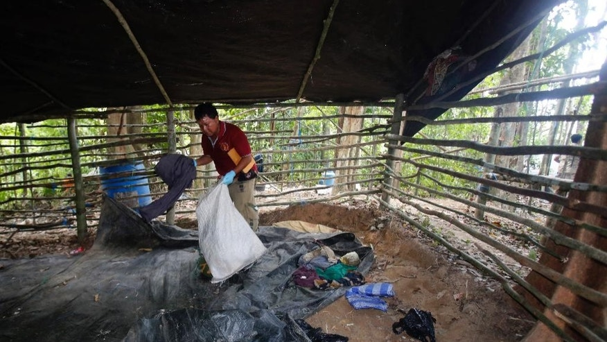 In this May 5, 2015 photo, forensic police officer collects items left at an abandoned migrant camp on Khao Kaew Mountain near the Thai-Malaysian border in Padang Besar, Songkhla province, southern Thailand. Thailand is eager to show its newfound toughness on human trafficking, taking reporters on patrols and tours of former camps, cooperating with neighboring countries and the U.S., and arresting dozens of officials - including a high-ranking officer in the military that now controls the country. A discovery of 36 bodies at abandoned traffickers' camps near Thailand's southern border with Malaysia has intensified international pressure on Thailand to crack down on smugglers. (AP Photo/Sakchai Lalit)
