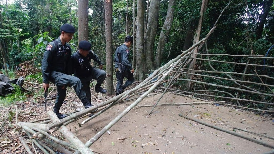 In this May 5, 2015 photo, border patrol police officers dismantle an abandoned migrant camp on Khao Kaew mountain near the Thai-Malaysian border in Padang Besar, Songkhla province, southern Thailand. Thailand is eager to show its newfound toughness on human trafficking, taking reporters on patrols and tours of former camps, cooperating with neighboring countries and the U.S., and arresting dozens of officials - including a high-ranking officer in the military that now controls the country. A discovery of 36 bodies at abandoned traffickers' camps near Thailand's southern border with Malaysia has intensified international pressure on Thailand to crack down on smugglers. (AP Photo/Sakchai Lalit)