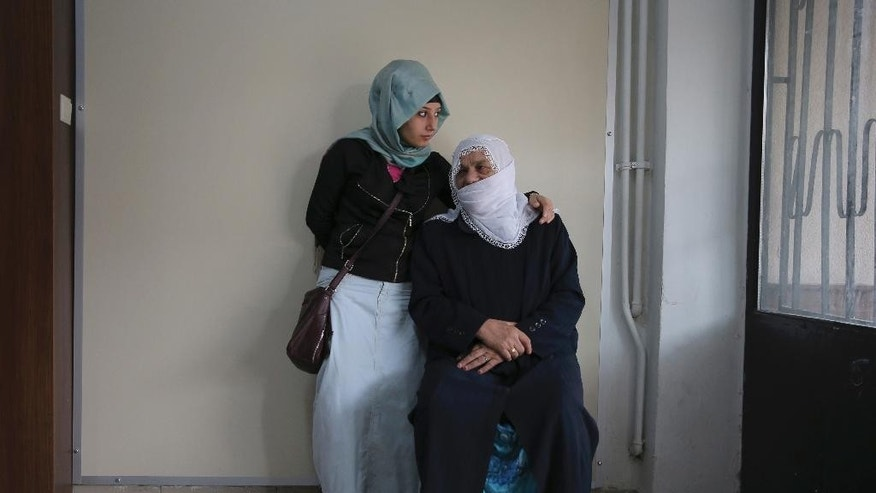 Two women wait to cast their votes in Sultanbeyli district of Istanbul, Turkey, Sunday, June 7, 2015. Turkey is holding a general election on Sunday and approximately 56 million Turkish voters are eligible to cast their ballots to elect 550 members of national parliament. (AP Photo)