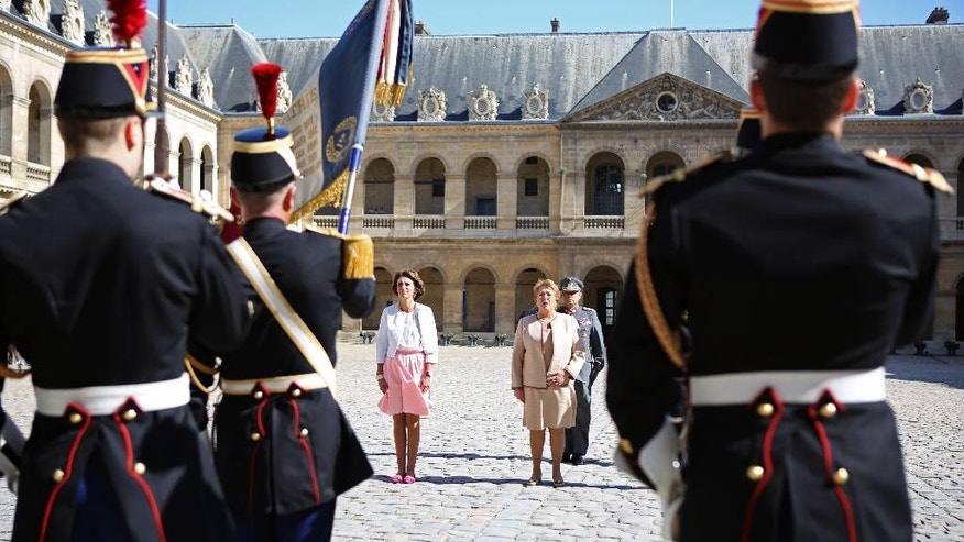 Chile President Michele Bachelet, center right, observes the French flag during a welcoming ceremony at the Invalides, after being greeted by French Social Affairs and Health Minister Marisol Touraine, left, in Paris, France, Monday June 8, 2015. Michele Bachelet is on a two-day official visit in France. (AP Photo/Remy de la Mauviniere/Pool)