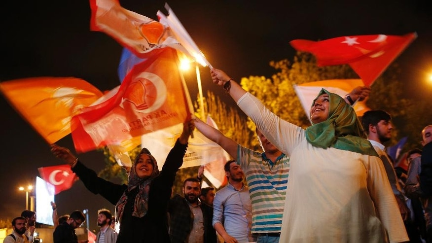 Supporters of Turkey's ruling Justice and Development Party celebrate after the election results in Istanbul, Turkey, late Sunday, June 7, 2015. With 99.9 percent of the vote counted, Erdogan's AKP had the support of around 41 percent of voters, state-run TRT television said. The unexpected setback for AKP likely puts an end, for the time being, to Erdogan's hopes of passing constitutional changes that would have greatly boosted the powers of his office. Instead, he faces struggles to retain his pre-eminent place in Turkish politics without the obvious levers to steer the government through his party in parliament. (AP Photo/Emrah Gurel)