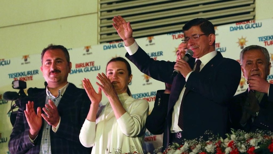 Turkey's Prime Minister and leader of ruling Justice and Development Party Ahmet Davutoglu, second right, waves to supporters from the balcony of his party in Ankara, Turkey, late Sunday, June 7, 2015. In a stunning rebuke of President Recep Tayyip Erdogan's ambitions to expand his powers, Turkish voters stripped his party of its simple majority in parliament, preliminary election results showed Sunday. With 99.9 percent of the vote counted, Erdogan's AKP had the support of around 41 percent of voters, state-run TRT television said. (AP Photo/Burhan Ozbilici)